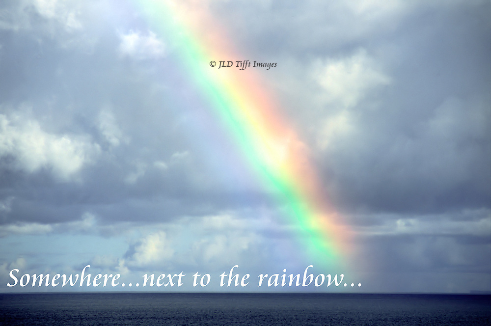 Rainbow over the sea with text: somewhere near the ebnd of the rainbow