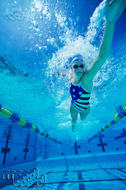 Woman swimming underwater (low angle view)