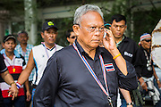26 NOVEMBER 2013 - BANGKOK, THAILAND: Former Deputy Prime Minister SUTHEP THAUGSUBAN, leader of the anti-government protests rocking Bangkok, talks on his mobile phone while walking through the Ministry of Finance complex. The Thai government issued as warrant for Suthep as the protests spread but he has not been arrested. Protestors opposed to the government of Thai Prime Minister Yingluck Shinawatra spread out through Bangkok this week. Protestors have taken over the Ministry of Finance, Ministry of Sports and Tourism, Ministry of the Interior and other smaller ministries. The protestors are demanding the Prime Minister resign, the Prime Minister said she will not step down. This is the worst political turmoil in Thailand since 2010 when 90 civilians were killed in an army crackdown against Red Shirt protestors. The Pheu Thai party, supported by the Red Shirts, won the 2011 election and now govern. The protestors demanding the Prime Minister step down are related to the Yellow Shirt protestors that closed airports in Thailand in 2008.     PHOTO BY JACK KURTZ