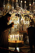 A Greek Orthodox priest lights a candle inside the Church of the Holy Sepulchre. In the background people pray before the Alter of the Crucifixion, where some Christians believe Jesus was crucified. (Jerusalem - October 4, 2010)