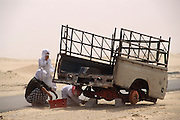 Kuwaitis on the Road to the Manageesh Oil Fields near the Saudi border, attempt to fix a trailer in a sandstorm. More than 700 wells were set ablaze by retreating Iraqi troops creating the largest man-made environmental disaster in history.