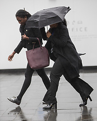 © Licensed to London News Pictures. 12/04/2017. Manchester, UK. Two women in the Spinningfields office district of Manchester battles against bitter winds and icy rain , which inverts umbrellas , during a sudden squall in Manchester City Centre . Photo credit: Joel Goodman/LNP