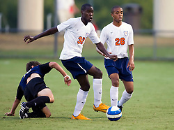 Virginia Cavaliers midfielder Tony Tchani (23) and Virginia Cavaliers defender Howard Turk (26) take the ball away from an ODU defender.  The Virginia Cavaliers defeated the Old Dominion Monarchs 3-0 in a pre-season NCAA Men's Soccer exhibition game held at Klockner Stadium on the Grounds of the University of Virginia in Charlottesville, VA on August 23, 2008.