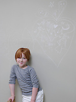 7-8 Year old girl stands below chalk drawing on wall