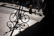The shadow of a locked up bike is on a central London street as a cyclist passes-by.