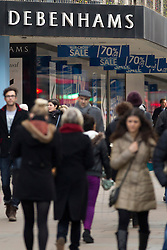 © Licensed to London News Pictures. 08/01/2013. London, UK.  Shoppers walk past Debenham's flagship store on Oxford Street in London today (08/01/13).  The department store chain today reported record December sales, achieved in part by additional promotions, with like-for-like sales rising by 2.9% compared to the same period in 2011/12 and online sales boosted by 39%.  Photo credit: Matt Cetti-Roberts/LNP