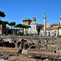 Description of Forum of Trajan in Rome, Italy<br /> The legacy of Emperor Trajan (reign 98 to 117 AD) was how his military prowess significantly expanded the Roman Empire. His territory included today's Britain, across southern Europe to Iraq (then Babylonia) and portions of Northern Africa. To celebrate his success and flaunt his power, he ordered architect Apollodorus of Damascus to create the Forum of Trajan. The resulting civic space was extravagant and expansive, measuring 1,000 by 600 feet ... the largest in history! The forum is in ruins yet the foundations remain. In the foreground was an enclosed courtyard. The marble flooring once displayed a gigantic equestrian statue of the emperor (called Equus Traiani) encircled by sculptures of captive enemies and military heroes. On the other side of the arches are rows of columns used to support Basilica Ulpia (the emperor's middle name). It was a very impressive 555 feet long. Column of Trajan is mostly intact. Its 600 feet of marble carvings tell the stories of the  emperor's military campaigns. The bronze statue of St. Peter at the 125 foot peak replaced the original version of Trajan. On either side were libraries. The two domes are relatively contemporary churches. On the left is Santa Maria di Loreto (Saint Mary of Loreto) built in 1596. On the right is Santissimo Nome di Maria (Most Holy Name of Mary) built in 1741.