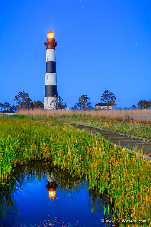 Bodie Island Lighthouse reflected in a small pond nestled into the marsh at twilight, on the Outer Banks of North Carolina.