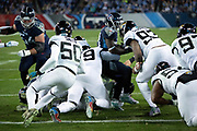 Tennessee Titans running back Dion Lewis (33) gets stuffed by Jacksonville Jaguars defensive tackle Marcell Dareus (99) and Jaguars defensive end Calais Campbell (93) as he runs the ball near the goal line during the week 14 regular season NFL football game against the Jacksonville Jaguars on Thursday, Dec. 6, 2018 in Nashville, Tenn. The Titans won the game 30-9. (©Paul Anthony Spinelli)