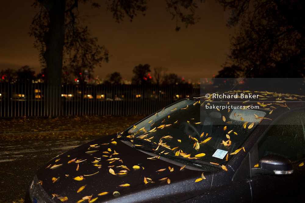 Autumnal leaves on the roof and bonnet (hood) of a parked car in the evening in a south London street, on 26th October 2017, in London, England.