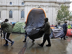 © Licensed to London News Pictures. 26/10/2011. London, UK. Protesters start to move tents and reorganise their site to facilitate the reopening of St Paul's. Occupy London protesters outside St Paul's Cathedral today, 26 October 2011. The UK's most popular Cathedral still has its doors closed over health and safety fears for it's visitors. Photo: Stephen Simpson/LNP