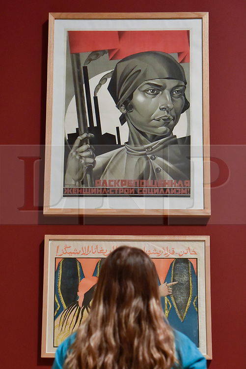 """© Licensed to London News Pictures. 07/11/2017. London, UK.  A student from Thomas Tallis School, Kidbrooke, south London, views """"Emancipated Woman:  Build Socialism!"""", 1926, by Adolf Strakhov, one of several Soviet political propaganda displayed at the preview of """"Red Star Over Russia: A Revolution in Visual Culture 1905-55"""" at Tate Modern.  The exhibition marks the centenary of the October Revolution and presents the visual history of Russia and the Soviet Union with works drawn from the late graphic designer David King. Photo credit: Stephen Chung/LNP"""