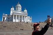 Senate Square; the lutheran Cathedral. Tourists taking souvenir photos.