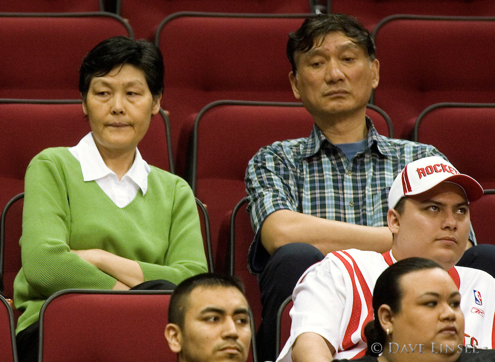 "Fang Fengdi (L) and Yao Zhiyuan (R) watch their son, Houston Rockets center Yao Ming play against the Detroit Pistons in Houston, Texas March 22, 2007. Fang is 6'3"" tall and Yao is 6'10"" tall. Yao Ming is 7'6"" tall. (Photo by Dave Einsel)"