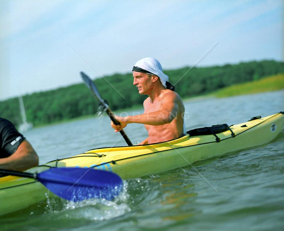 Shirtless man kayaking in East Hampton, NY