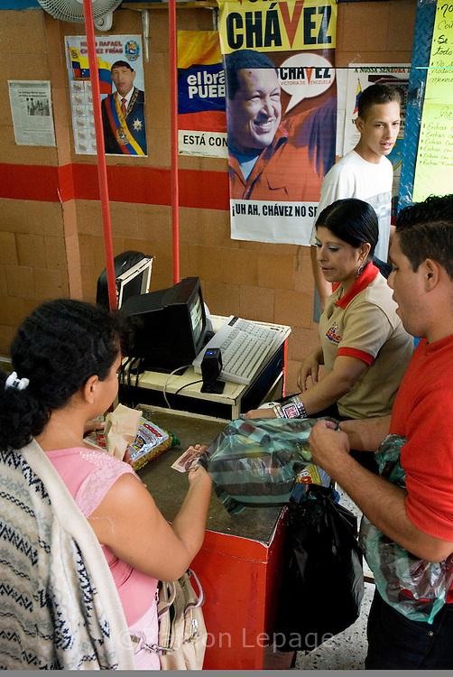 Consumidores venezolanos compran comida en Mercal del centro de Caracas, mercado auspiciado por el gobierno venezolano. Muchas personas compran bienes debido al gran flujo de gastos de gobierno, créditos bancarios privados y el miedo a la inflación.  Uno de los hechos económicos más importantes, en estos años, ha sido el control monetario impuesto por la administración de Chávez, colocando el precio del dólar a 2150 bolívares mientras que en el mercado negro se vende de 3500 a 4200 bolívares, y limitando el cupo de consumo en gastos electrónicos y de viajes. Caracas, 6-03-07 (Ramón Lepage/Orinoquiaphoto)  Venenezuelan consumers buying food at the government sponsored Mercal food chain store in downtown Caracas, March 06, 2007. Many people are buying goods due to the large cash flow from government spending, enticing private bank loans and also fears of inflation in the economy. The Chavez adminitration implemented more than 3 years ago a currency control, setting the the price of 2150 bolivares per dollar while the black market price is about 3500 to 4200 bolivares. Venezuelans are allowed to spend during the year up to  $ 5000 for travel and $3000 for internet shopping. (Ramón Lepage/Orinoquiaphoto)