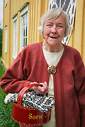 Sofie Marstad (88), veteran i selbustrikk. Her med sin egen bindingskorg og et par vanter i selbustrikk. Foran Selbu bygdemuseum, i den gamle prestegården.