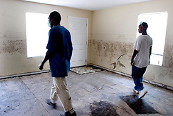 30 Sept, 2005. New Orleans, Louisiana. Lower 9th ward. Hurricane Katrina aftermath. <br /> The remnants of the lives of ordinary folks, now covered in mud as the flood waters remain. Residents return to inspect the damage to their buildings. In this case the mould grows thick on the walls.<br /> Photo; ©Charlie Varley/varleypix.com