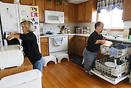 Chris Kotzian (R) and wife Barb clean up in their kitchen in Thornton, Colorado March 25, 2010.  Both about four-feet-tall,  the Kotzians are both achondroplasia dwarfs, a rare genetic disorder of bone growth.  Preferring to be called little persons they both are active in the Little People of America, the only dwarfism support organization that includes all 200+ forms of dwarfism.  REUTERS/Rick Wilking (UNITED STATES)