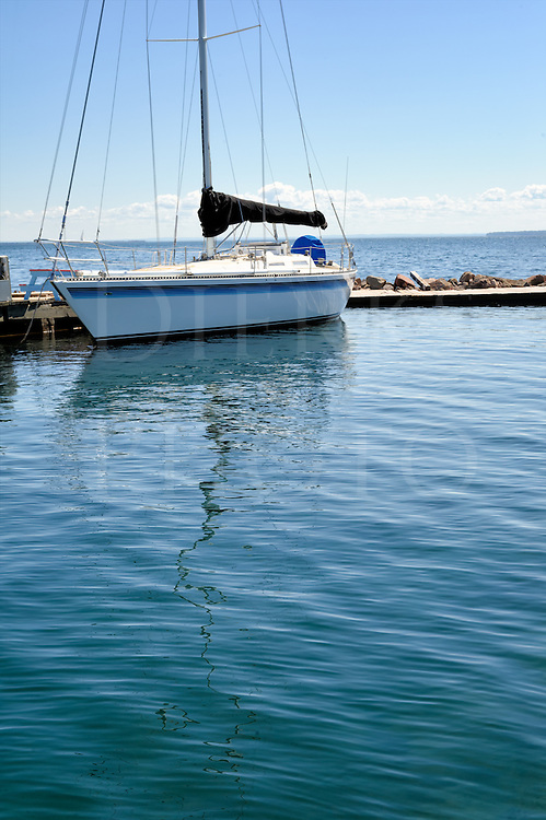 Solitary sailboat on calm rippled water, tied to jetty dock, sailing background image with copy space.