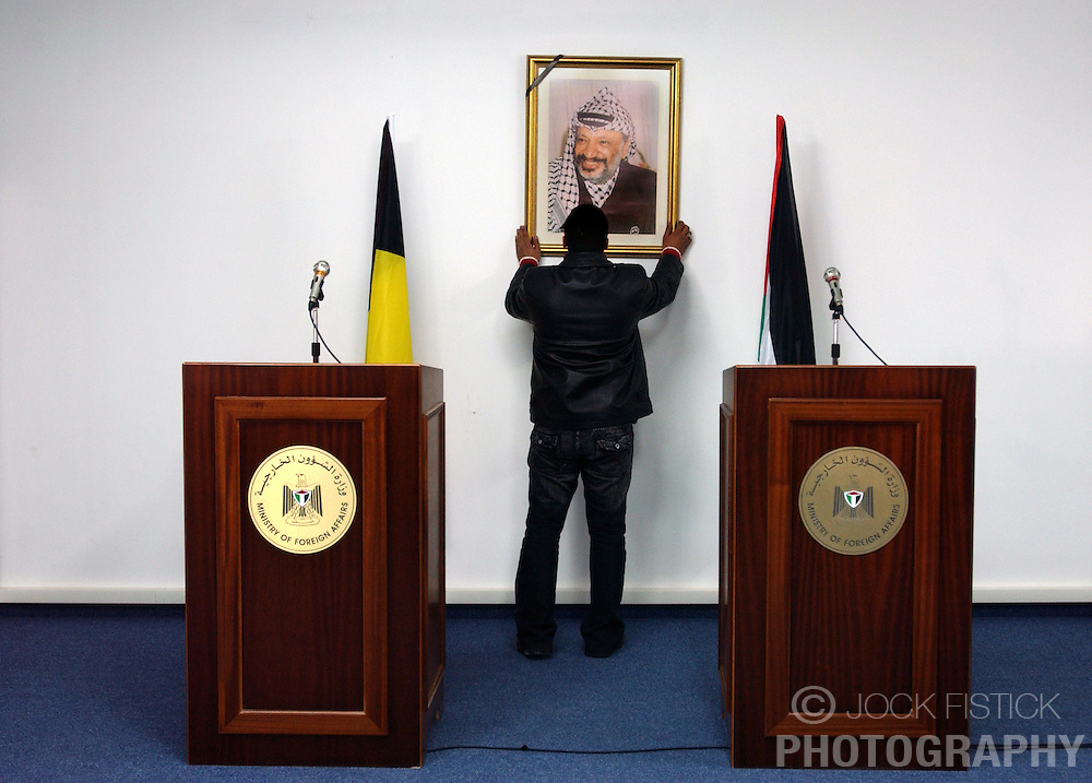 A portrait of the late Yasser Arafat with a black arm-band hung on the frame, is straightened, before the start of a news conference at the Palestinian Authority's Ministry of Foreign Affairs office in the West-bank city of Ramallah. The black arm band commemorated Arafat's recent passing on Nov. 11, 2004. (Photo © Jock Fistick)