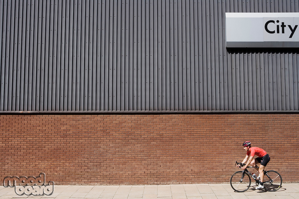 Man cycling past building with 'City' written on side