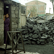 Families live close to the mines.  Their homes and lifestyle is connected to mining and to the use of coal.  A woman and child outside their home.