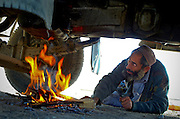 Arkansas Democrat-Gazette/BENJAMIN KRAIN 11-10-03<br /> Trucks carrying returning refugees from Pakistan often are in poor condition. Here a returning refugee builds a fire underneath his engine hoping to warm the oil enough to start the truck. &quot;The battery is good,&quot; one man traveling with him said, &quot;but the engine is weak.&quot; This truck started about 20 minutes after the man lit the fire.