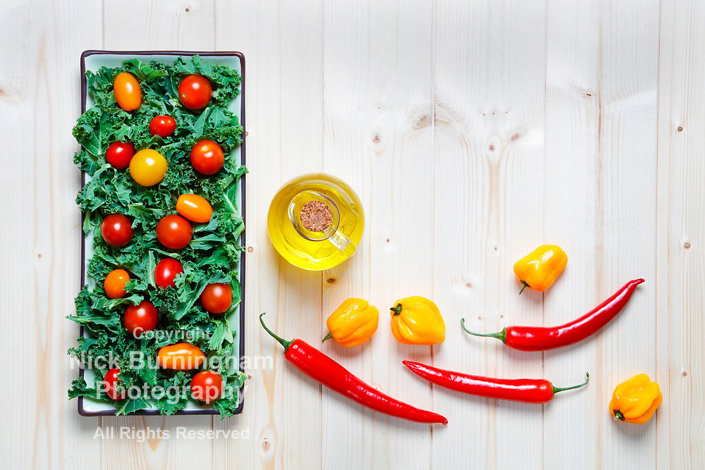 Fresh chopped prepared kale with yellow and red cherry tomatoes on plate with knife and hott red and yellow chilli peppers and olive oil with copy space