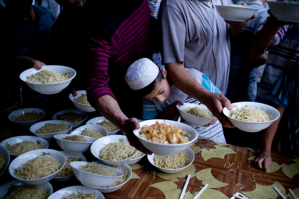 Uyghur men receive free meal at mosque before the break of  Ramadan in Hotan, Xinjian province in China.