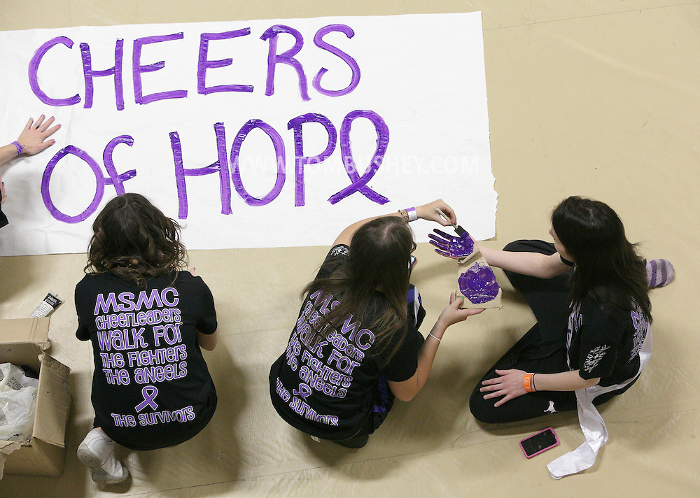 Mount Saint Mary student Gianna Pelliccia, center, of the Cheers of Hope team paints Christina Sica's hand before the start of the Relay for Life at the Kaplan Recreation Center in Newburgh on Friday, March 22, 2013. The team is made up of Mount Saint Mary cheerleaders.