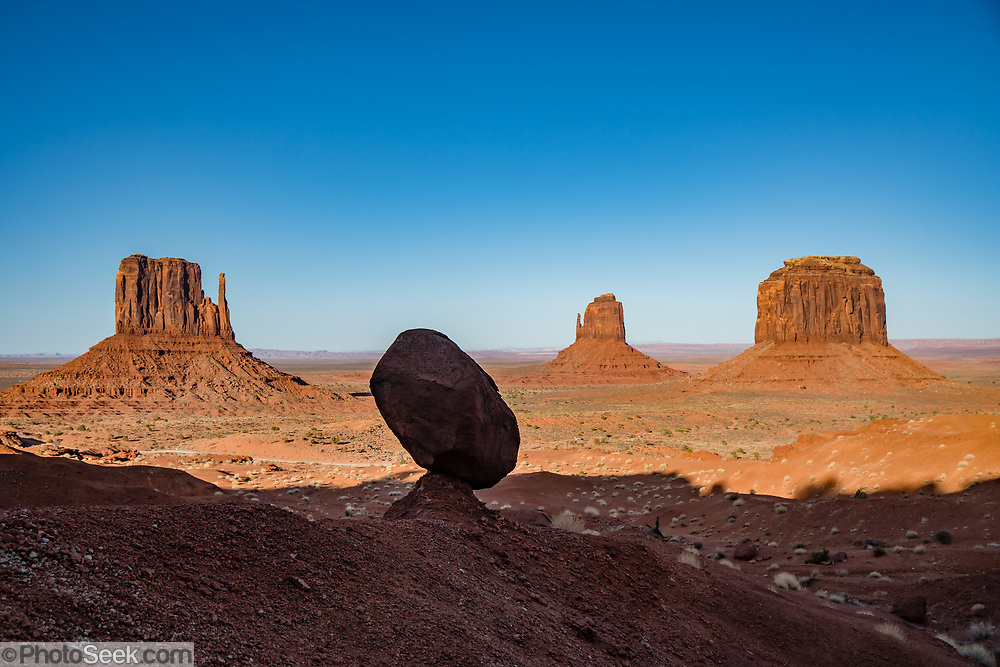 West and East Mitten Buttes and Merrick Butte punctuate the horizon beyond a balanced rock in Monument Valley Navajo Tribal Park, Arizona, USA. The Western movie director John Ford set several popular films here.