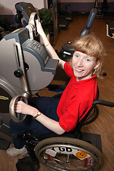 Access to services, Disabled woman in the gym; using Ergometer,