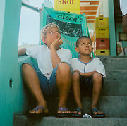 Two small boys sitting on some steps looking at something above them Brazil