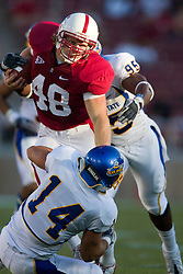 September 19, 2009; Stanford, CA, USA;  Stanford Cardinal fullback Owen Marecic (48) is tackled by San Jose State Spartans linebacker Travis Jones (14) and defensive end Carl Ihenacho (95) after a pass reception during the first quarter at Stanford Stadium. Stanford defeated San Jose State 42-17.
