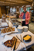 Breakfast buffet at Griesalp Hotel Berghaus, Kiental, Switzerland, Europe. The village of Griesalp is in the municipality of Reichenbach im Kandertal. Above the beautiful lake of Oeschinnensee, easily reached by lift from Kandersteg, is a challenging hike traversing steeply up over Hohtürli Pass then down to Griesalp in the remote valley of Kiental. Ascend 1120 meters and descend 1380 m in 13 km, which feels much longer due to steep, exposed rocky & gravelly slopes. Stairs and ladders assist your footing. Optionally stay overnight in Blüemlisalp hut at Hohtürli Pass. For licensing options, please inquire.