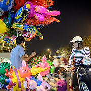 A young Vietnamese girl admires the helium balloons for sale on a street in Hanoi's Old Quarter, as her mother looks on.