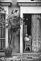 Front view from street of San Juan home with man reading paper