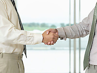 Businessmen Shaking Hands in front of window side view close-up