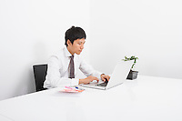 Asian mid adult businessman using laptop at desk in office