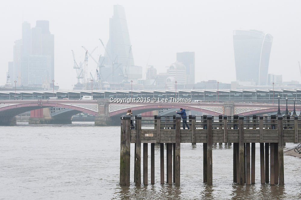 Central London, UK. 19th March 2015.  Health alert as potentially lethal smog hits Britain. Pictured: A tourist takes photographs with the City of London skyline in the distance.  // Lee Thomas, Flat 47a Park East Building, Bow Quarter, London, E3 2UT. Tel. 07784142973. Email: leepthomas@gmail.com. www.leept.co.uk
