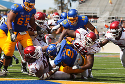 September 24, 2011; San Jose, CA, USA; San Jose State Spartans running back Brandon Rutley (9) is tackled by New Mexico State Aggies linebacker Boyblue Aoelua (47) and defensive end Pierre Fils (48) near the goal line during the second quarter at Spartan Stadium.