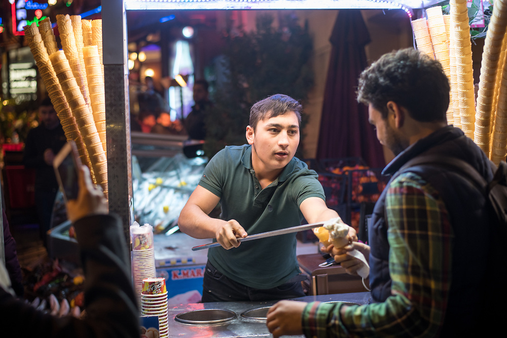 Young adult male serves customer ice-cream from food cart on the streets of Istanbul, Turkey