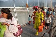 People crossing the Ramjula bridge over the river Ganges in Rishikesh, Uttarakhand, India