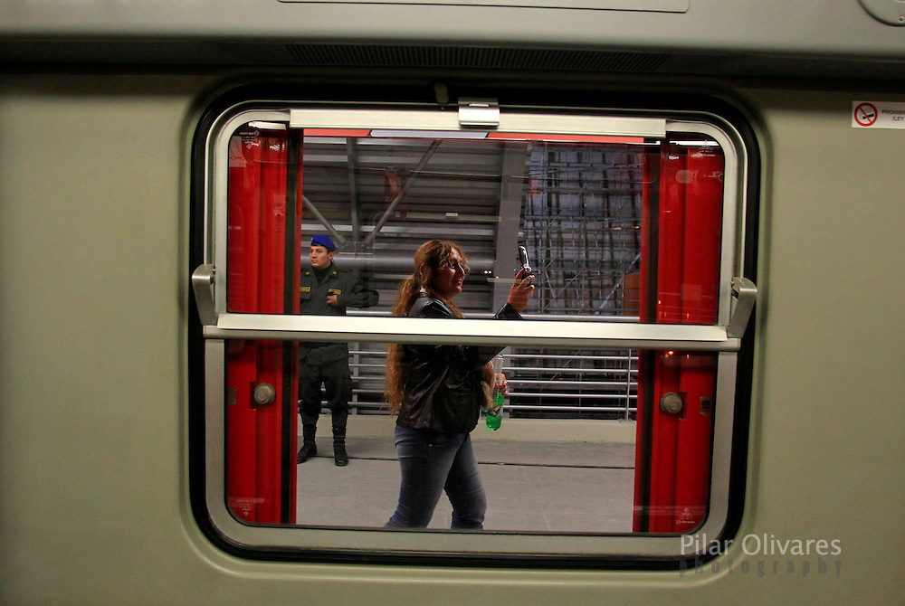 A woman takes pictures using her mobile phone of the elctric train during the train testing in Lima. (photo: Pilar Olivares)