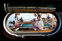 Local fishermen in Sumbawa Indonesia approach our boat to trade fish and seafood for cigarettes and alcohol and magazines.  I was down below when they approached and snuck this shot through the window.