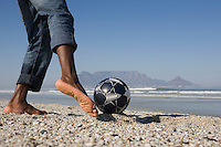 Man playing soccer on beach low section