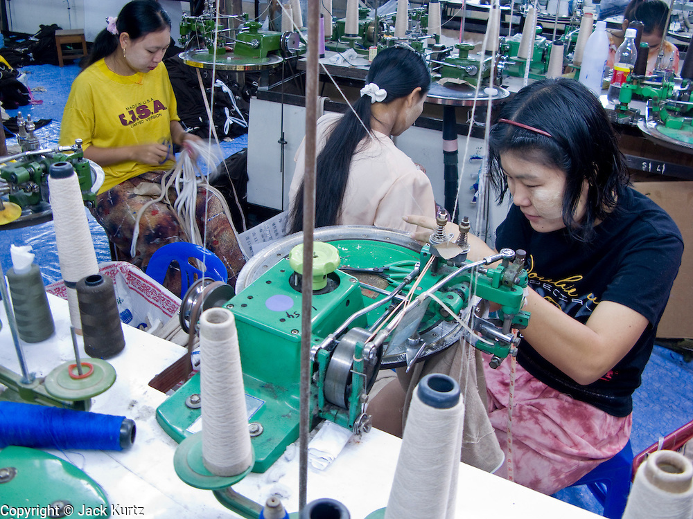 """25 FEBRUARY 2008 -- MAE SOT, TAK, THAILAND: Illegal Burmese workers in a sewing factory in Mae Sot, Thailand. The factory owner allegedly bribes Thai officials not to raid his place. Workers here work seven days a week, 14 hours per day and make about $5 US per day. Their housing, which is provided by the factory owner, is in the factory compound. There are millions of Burmese migrant workers and refugees living in Thailand. Many live in refugee camps along the Thai-Burma (Myanmar) border, but most live in Thailand as illegal immigrants. They don't have papers and can not live, work or travel in Thailand but they do so """"under the radar"""" by either avoiding Thai officials or paying bribes to stay in the country. Most have fled political persecution in Burma but many are simply in search of a better life and greater economic opportunity.  Photo by Jack Kurtz"""