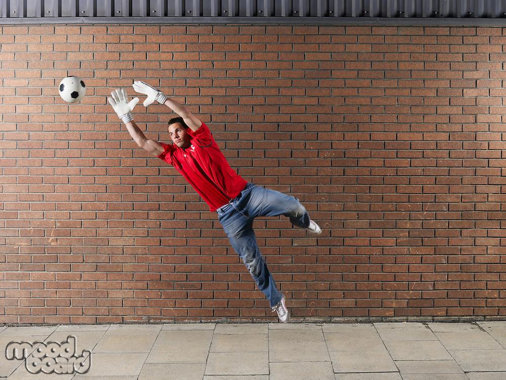 Goalkeeper reaching for football against brick wall