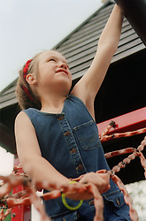 Young girl playing on climbing frame in adventure playground,